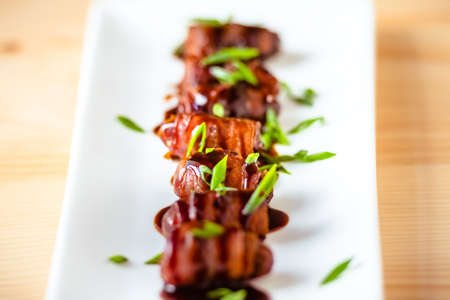 green dates: Snack appetizer - dried dates wrapped with bacon and dressed with balsamic creme vinegar and green onions. Selective focus