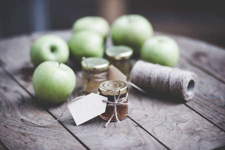 Apple jam in a small glass jar and green apples on wooden table. Blank label provides copy space for a message. Toned image photo