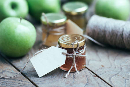 jam jar: Apple jam in a small glass jar and green apples on wooden table. Blank label provides copy space for a message