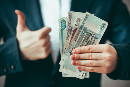 roubles: Business person holds roubles and shows thumb up. Toned image