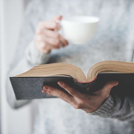 Young woman reading a book and holding cup of tea or coffee. Toned image Imagens