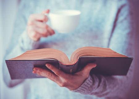 book: Mladá žena čtení knihy a držení šálku čaje nebo kávy. Tónovaný obraz Reklamní fotografie