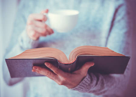 mujer leyendo libro: Mujer joven que lee un libro y la celebración de taza de té o café. Imagen entonada Foto de archivo
