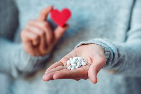 persona enferma: P�ldoras blancas y coraz�n de papel en las manos. Medicina y salud concepto