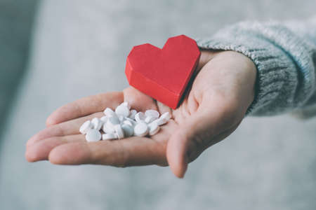 White pills and paper heart in hands. Medicine and health care concept. Toned image Imagens
