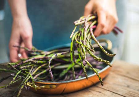 食べ物: 新鮮なアスパラガスの束を持って手。選択したフォーカス