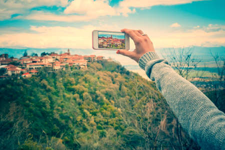 romantic picture: Person with smart phone makes pictures of beautiful old city from the hill. Toned picture Stock Photo