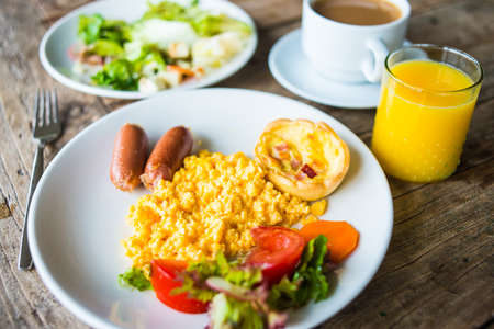 scrambled eggs: Breakfast on wooden table - scrambled eggs, salad, fresh orange juice and coffee