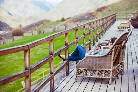 woman lying: Girl sitting on terrace with beautiful mountain view