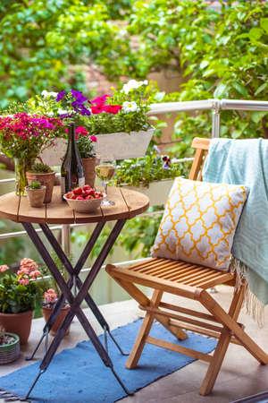 Hermosa terraza o balcón con una pequeña mesa, una silla y flores Foto de archivo
