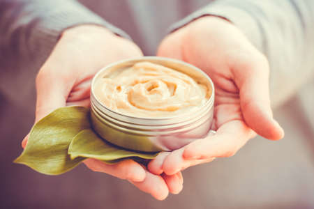 Cosmetic cream container with green herbal leaves in woman hands. Toned image Standard-Bild