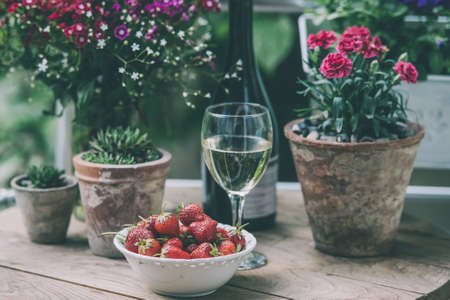 Strawberry, glass of wine and flowers on small wooden table on beautiful terrace or balcony. Toned image