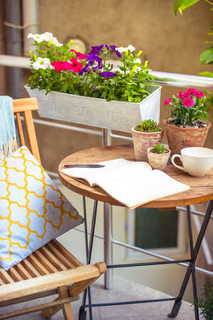 wooden furniture: Beautiful terrace or balcony with small table, chair and flowers
