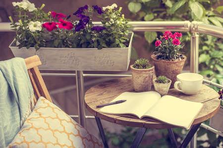 silla: Hermosa terraza o balcón con una pequeña mesa, una silla y flores. Imagen entonada