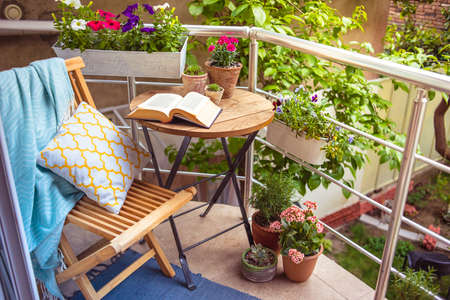 silla de madera: Hermosa terraza o balcón con una pequeña mesa, una silla y flores Foto de archivo