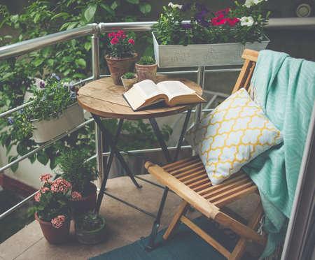 Hermosa terraza o balcón con una pequeña mesa, una silla y flores. Imagen entonada