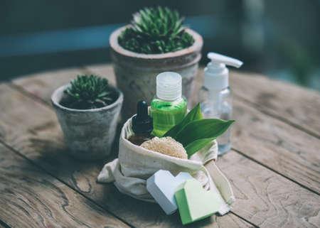 Cosmetische fles containers met groene kruiden bladeren en tuin potten met bloemen op houten achtergrond. Getinte afbeelding