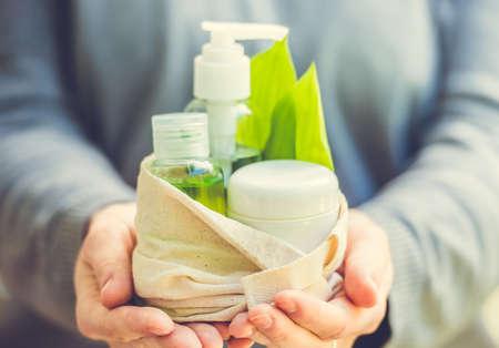 organic cotton: Bottiglia contenitore cosmetici con foglie di erbe verdi in piccola borsa in cotone biologico nelle mani di donna. Tonica immagine. Messa a fuoco selettiva
