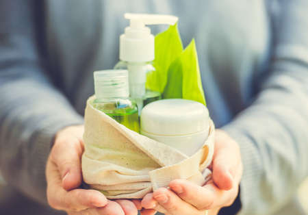 Cosmetic bottle container with green herbal leaves in small organic cotton bag in woman hands. Toned image. Selective focus Stockfoto