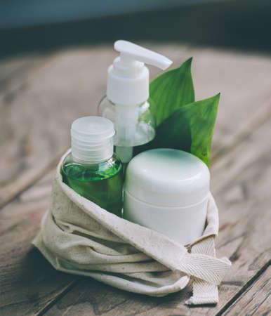 organic cotton: Bottiglia contenitore cosmetici con foglie verdi di erbe in piccolo sacchetto di cotone organico su sfondo di legno. Tonica immagine