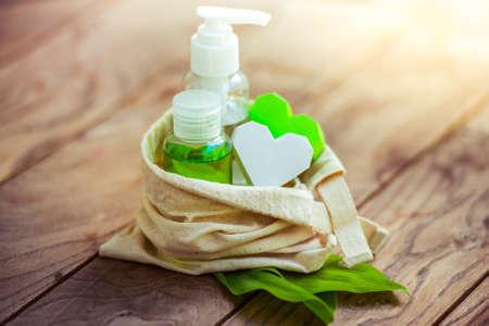 organic cotton: Contenitori bottiglia cosmetica in piccolo sacchetto di cotone organico con foglie verdi di erbe sul fondo in legno