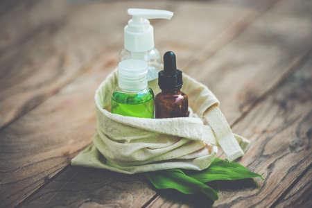 organic cotton: Contenitori bottiglia cosmetica in piccolo sacchetto di cotone organico con foglie verdi di erbe su sfondo di legno. Tonica immagine Archivio Fotografico