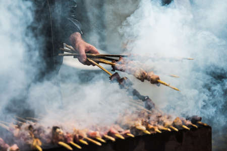Preparation of barbecue on grill. Roasted meat slices shashlik. Selective focus and shallow DOF