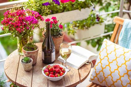 sillon: Hermosa terraza o balc�n con una peque�a mesa, una silla y flores Foto de archivo