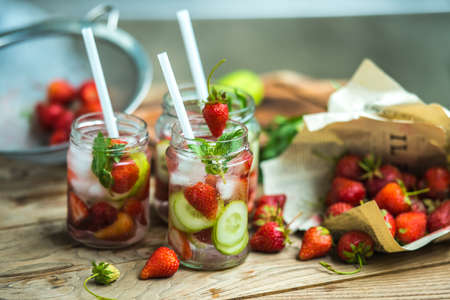 cocktail drinks: Three retro glass jars of lemonade with  strawberries, cucumber and mint on wooden table Stock Photo