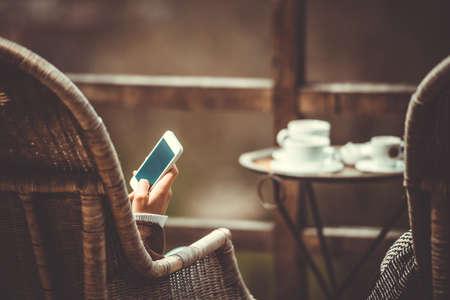 Person sitzen im Kaffeehaus mit Smartphone in den Händen. Getönt
