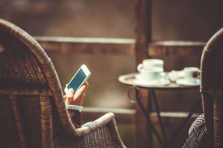 Persoon zitten in cafe met smartphone in handen. Gestemd beeld Stockfoto