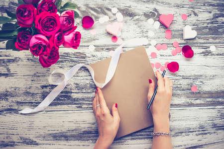 Blumenstrauß aus Rosen und geschlossenes Buch oder Notebook in weibliche Hände auf alten Holztisch. Draufsicht. Getönt Lizenzfreie Bilder