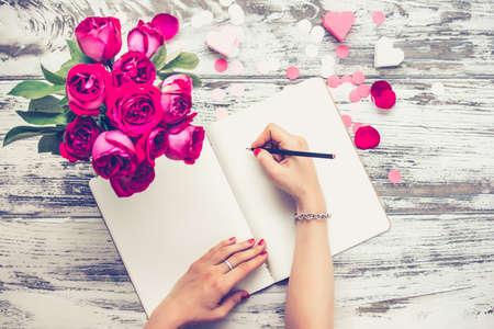 Vrouwelijke handen schrijven in open notebook en boeket rozen op oude houten tafel. Bovenaanzicht. Getinte afbeelding