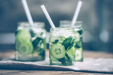 Three retro glass jars of lemonade with cucumber and mint on wooden table. Toned image Archivio Fotografico