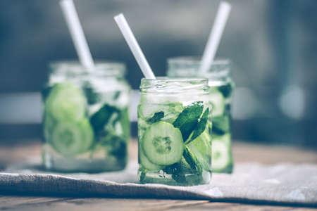 limonada: Tres tarros de cristal retro de limonada con pepino y menta en la mesa de madera. Imagen entonada