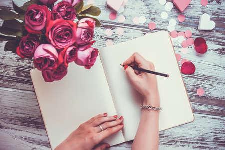 Manos femeninas escribiendo en el cuaderno abierto y ramo de rosas en la mesa de madera vieja. Vista superior. Imagen entonada Foto de archivo - 40646166