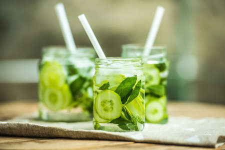 Three retro glass jars of lemonade with cucumber and mint on wooden table Archivio Fotografico