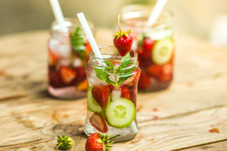 cucumber: Three retro glass jars of lemonade with  strawberries, cucumber and mint on wooden table Stock Photo