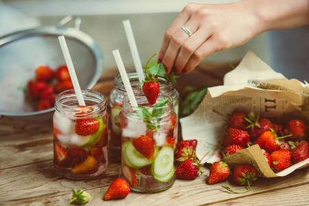 limonada: Preparación de limonada - tres frascos de vidrio retro, fresas, pepino y menta en la mesa de madera. Imagen entonada Foto de archivo