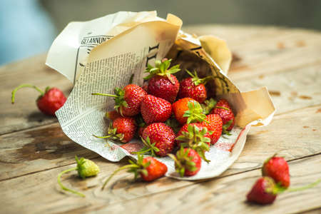 old newspaper: Fresh strawberries in old newspaper on wooden table