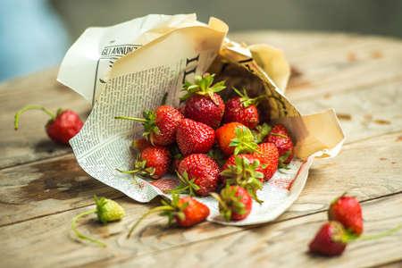 oude krant: Verse aardbeien in de oude krant op houten tafel