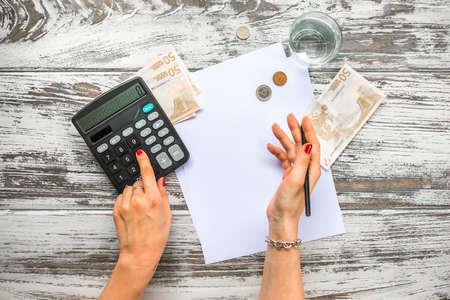 dinero: Mujer que cuenta el dinero del euro con la calculadora. Concepto de negocio. Vista superior Foto de archivo