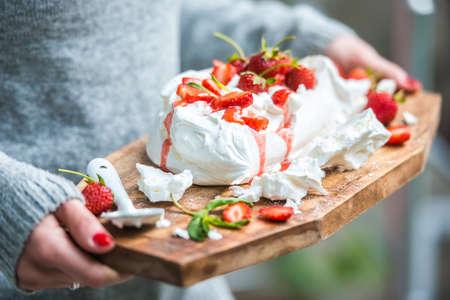 uk cuisine: Classic british summer dessert called Eton Mess. Strawberries, crushed meringue and whipped cream on wooden board Stock Photo