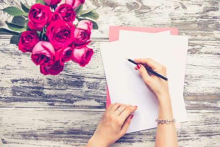 mujer con rosas: Escritura de la mujer en las hojas de papel en blanco en la mesa de madera vieja. Vista superior. Imagen entonada