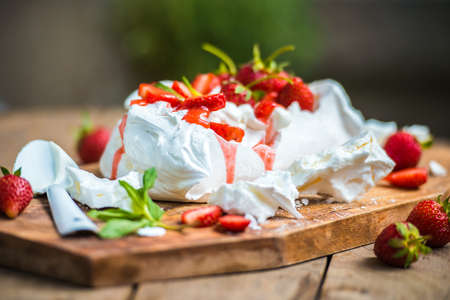 Classic british summer dessert called Eton Mess. Strawberries, crushed meringue and whipped cream on wooden board Фото со стока