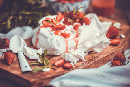 british food: Classic british summer dessert called Eton Mess. Strawberries, crushed meringue and whipped cream on wooden board. Toned image