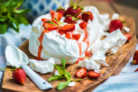 Classic british summer dessert called Eton Mess. Strawberries, crushed meringue and whipped cream on wooden board 스톡 콘텐츠