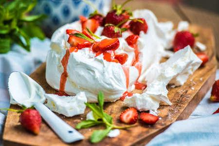 postres: Postre de verano británico clásico llamado Eton Mess. Fresas, merengue picado y crema batida en tabla de madera Foto de archivo