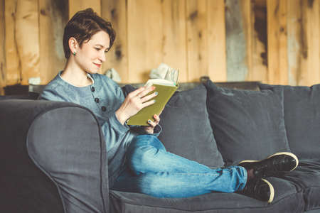Young beautiful woman reading a book on sofa