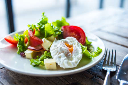 raddish: Fresh vegetable salad with poached egg on wooden background
